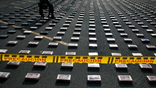 A Colombian anti-drugs police officer arranges packages of cocaine