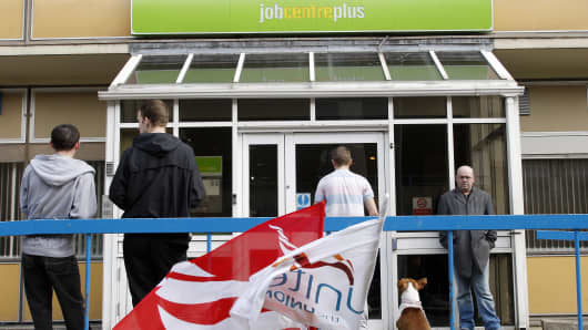 People stand outside the Job Centre in Chatham, in south-east England