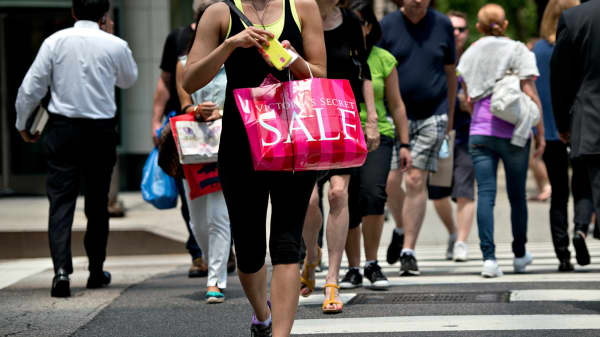 A woman carries a Victoria's Secret shopping bag as she walks through a retail area known as the 'Magnificent Mile' in Chicago, Illinois.