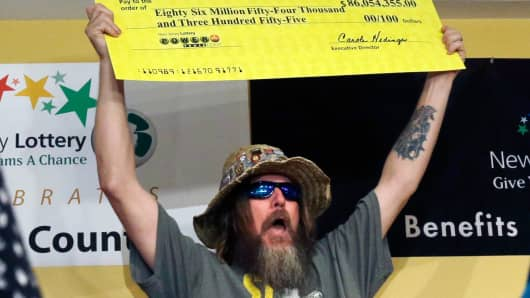 Lottery winner William L. Seeley shouts as he holds up a sign made as a check Tuesday, Aug. 13, 2013, in Toms River, N.J.