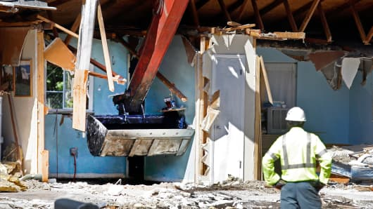 An excavator checks the sinkhole in the bedroom of the home of Jeff Bush during demolition March 4, 2013, in Seffner, Fla.