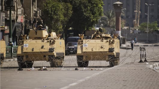 Egyptian army armored personnel carriers (APC) are seen stationed at the entrance of Tahrir Square on August 18, 2013 in Cairo.