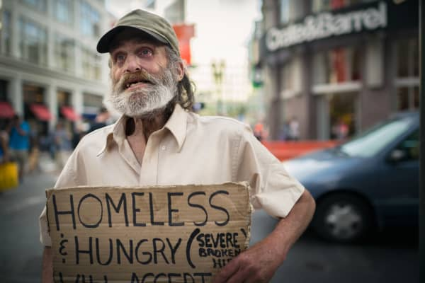 A homeless man holding a sign asking for a donation from bystander in San Francisco, California.