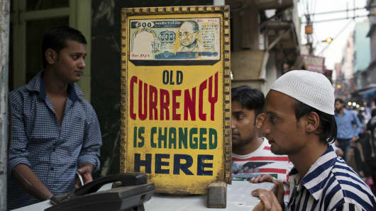 Men wait at a currency exchange counter in Old Delhi. Indians working abroad are capitalizing on the weak rupee to send more money back home.