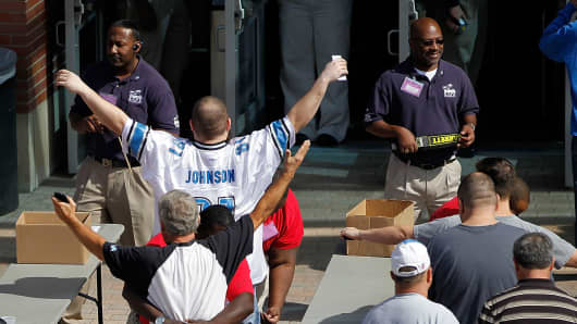 Football fans go through security checks before entering Ford Field prior to the start of a game in Detroit.
