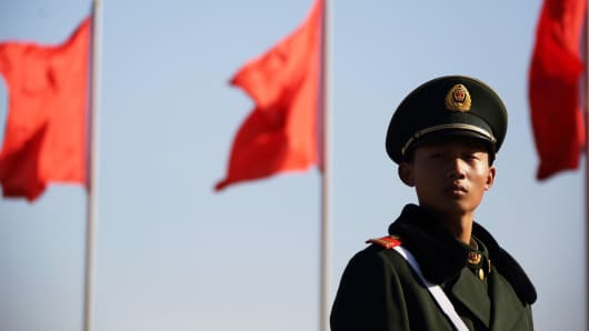 A paramilitary police officer stands guards in front of flags at Tiananmen Square in Beijing.