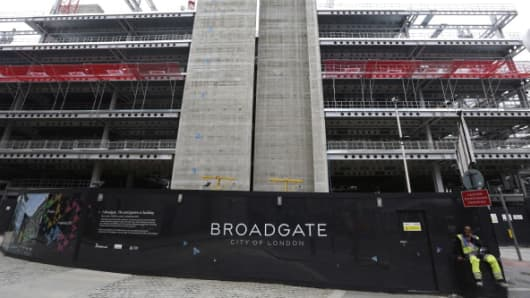 A construction worker sits outside the building site of No. 5 Broadgate in London.