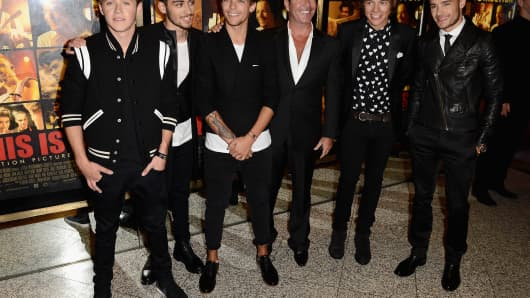 "Simon Cowell (C) with the boy band One Direction, who appeared on the 2010 version of ""The X Factor"""