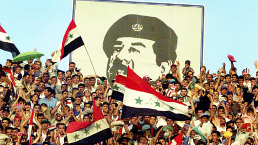 Baghdad residents cheer under an image of President Saddam Hussein in 2001.
