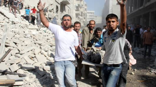 Syrians men evacuate a victim following an air strike by regime forces in the northern city of Aleppo on August 26, 2013.