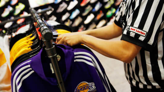 An employee arranges racks of jackets at the House Of Hoops by Foot Locker retail store at the Beverly Center in Los Angeles, California.