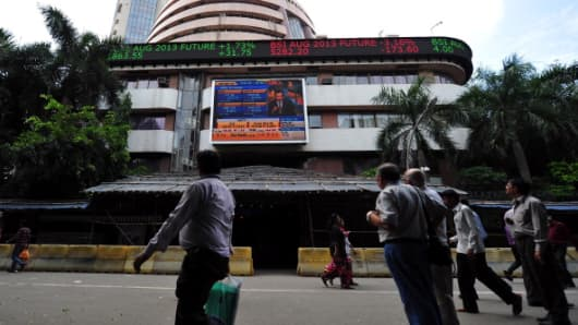 Onlookers watch share prices on the Bombay Stock Exchange (BSE) during intra day trade on August 27, 2013