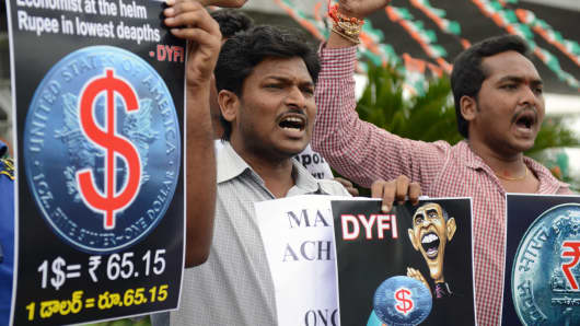 Democratic Youth Federation of India activists hold placards as they shout slogans during their protest over the rupee's fall in Hyderabad on August 23.
