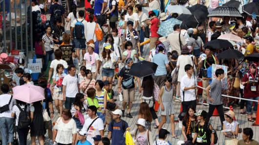 Pedestrians and shoppers walk through the Odaiba area of Tokyo, Japan.