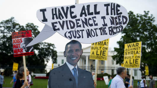 A cutout of President Barack Obama stands on the sidewalk as demonstrators march in protest during a rally against a possible US and allies attack on Syria.
