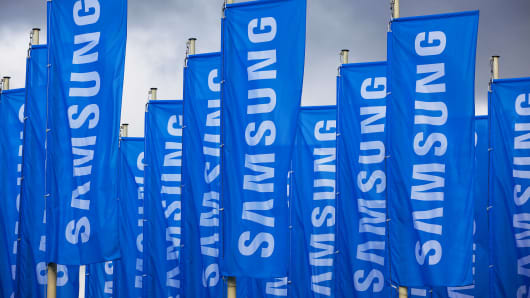 The Samsung Electronics Co. Ltd logo sits on banners flying outside the venue ahead of the opening of the IFA consumer electronics show in Berlin, Germany, on Wednesday, Sept. 4, 2013.