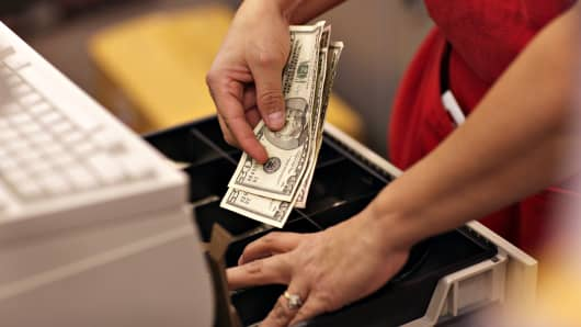 A cashier puts cash into a register inside a Super Target store in Thornton, Colorado.