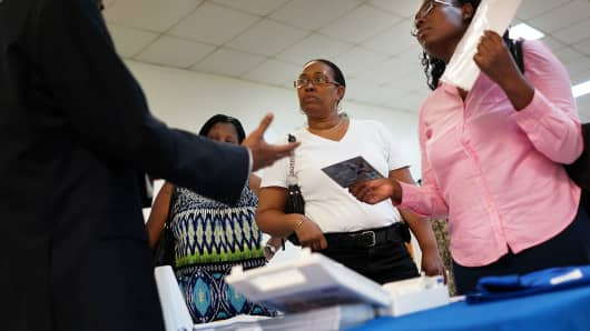 Job seekers speak with an employment recruiter in Brooklyn, NY