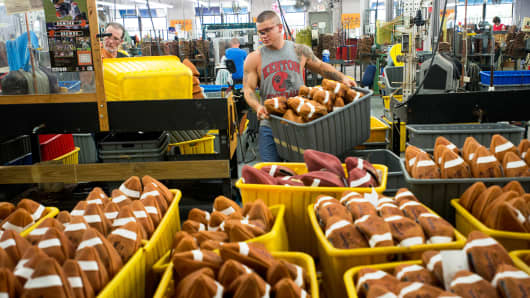 A worker carries a tote full of turned, non-inflated footballs to the quality control area at the Wilson Football Factory in Ada, Ohio