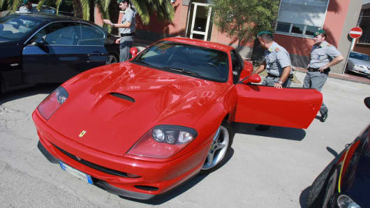 Police inspect luxury cars seized during a crackdown on the Camorra mafia in southern Italy