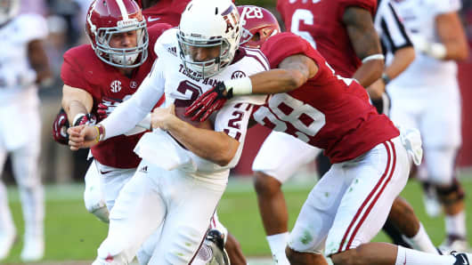 Quarterback Johnny Manziel #2 of the Texas A&M Aggies is tackled by defensive back Vinny Sunseri #3 and defensive back Dee Milliner #28 of the Alabama Crimson Tide during the game at Bryant-Denny Stadium on November 10, 2012 in Tuscaloosa, Alabama.