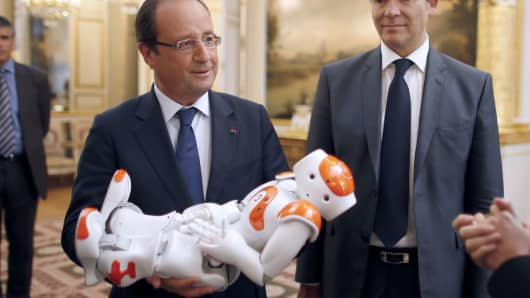 France's President Francois Hollande (L), flanked by French Minister for Industrial Recovery Arnaud Montebourg (R), holds an humanoid robot 'Nao' from Aldebaran Robotics company as he visits an exhibition on French industrial design and technology.