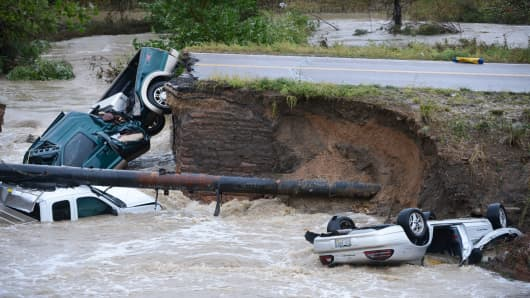 Three vehicles crashed into a creek close after the road washed out from beneath them in Broomfield Colorado, September 12, 2013.