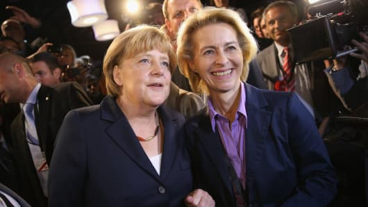 German Chancellor Angela Merkel (L) chats with journalists and Minister of Work and Social Issues Ursula von der Leyen (R).