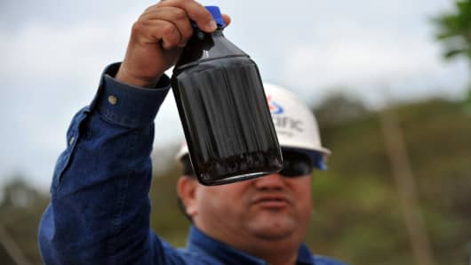 An engineer of Canadian oil company Pacific Rubiales shows a sample of heavy crude oil extracted from several wells (clusters) of Colombia's main oilfield Rubiales, in Meta department, Colombia.