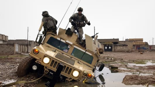 U.S. Army soldiers dismount from their Humvee after getting stuck in a mud hole in Kirkuk, Iraq, 2006.