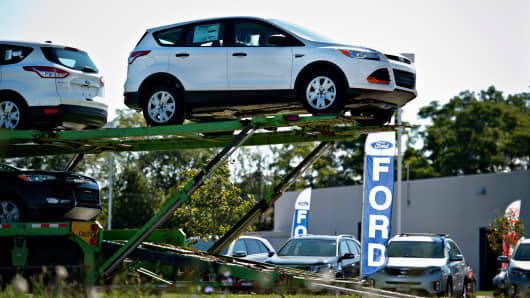 2014 Ford Escape vehicles sit on a car carrier outside of the Bill Walsh Ford car dealership in Ottawa, Illinois, Sept. 3, 2013.