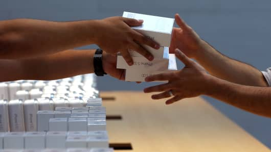 Apple Store employees pass boxes of the new Apple iPhone 5S in Palo Alto, Calif.
