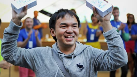 Jimmy Gunawan proudly shows his new iPhones outside Apple's flagship store in Sydney.