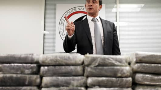 French Interior minister Manuel Valls talks to journalists in front of cocaine seized by French police, on September 21, 2013 in Nanterre, France.
