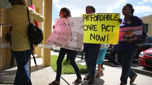 Protesters walk into the office of Florida State Rep. Manny Diaz as they protest his stance against the expansion of healthcare coverage on September 20, 2013 in Miami, Florida.