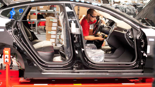 An employee works on a Telsa Model S sedan on an assembly line at the company's assembly plant in Fremont, Calif.