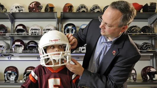 Stefan Duma, head of the Virginia Tech-Wake Forest School of Biomedical Engineering and Sciences, fits a football helmet. Youth football players wear the same size helmets as adult players, but with more padding to fit.