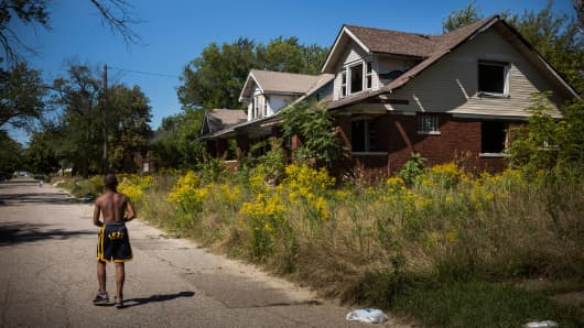 Lawrence Payne walks past two abandoned houses on September 4, 2013 in the Six Mile Gratiot neighborhood of Detroit, Michigan.