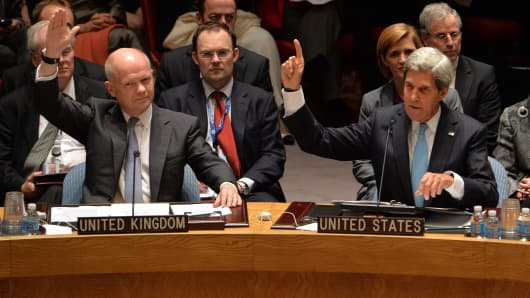 Britain's Foreign Minister William Hague (L) and US Secretary of State John Kerry (R) vote to approve a resolution that will require Syria to give up its chemical weapons during a meeting September 27, 2013 at UN headquarters in New York.