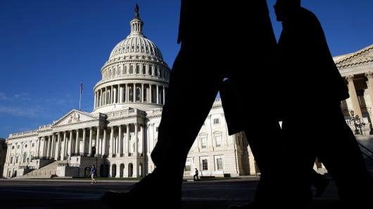 Pedestrians pass the U.S. Capitol.