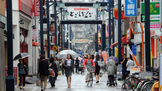 Pedestrians walk through the Togoshi shopping district in Tokyo, October 1, 2013.