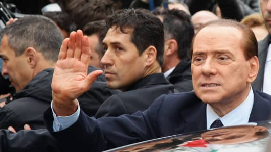 Silvio Berlusconi waves after the preliminary hearing of the Mediatrade case at court