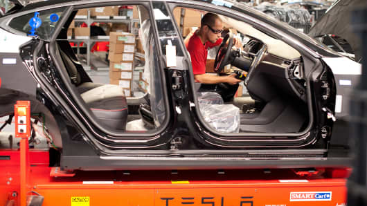 An employee works on a Telsa Motor Model S sedan as it makes its way along an assembly line at company's assembly plant in Fremont, Calif.