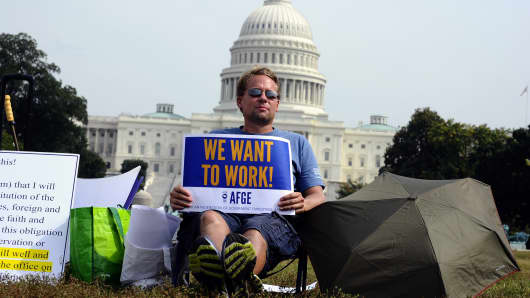 A protester displays a placard as he joins others in a demonstration in front of the US Capitol in Washington, DC, urging congress to end the federal government shutdown, October 3, 2013.