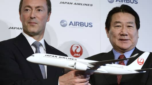 Fabrice Bregier, chief executive officer of Airbus SAS, left, and Yoshiharu Ueki, president of Japan Airlines Co. (JAL), holds a model of an Airbus A350 aircraft during their joint news conference in Tokyo, Japan,