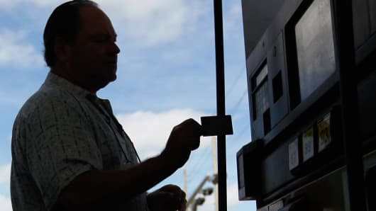 A man uses a credit card to pay for gas in Miami, Florida.