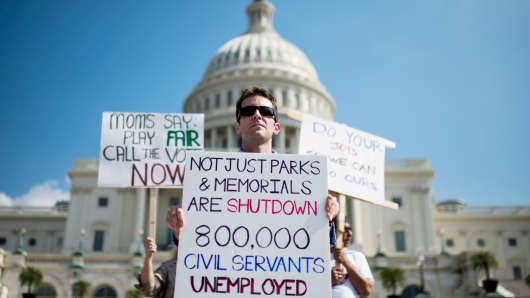 A government scientist stands with other federal workers at the Capitol