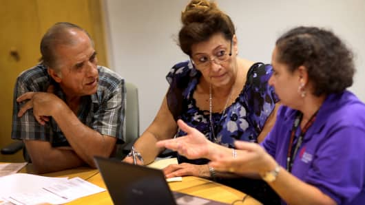 Affordable Care Act navigator Nini Hadwen (R) speaks with Jorge Hernandez (L) and Marta Aguirre as they shop for health insurance in Miami.