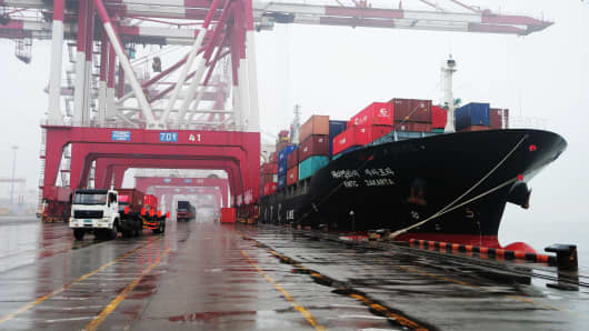 Trucks arrive with containers to be loaded on to a ship at the Qingdao port, in northeastern China's Shandong province.
