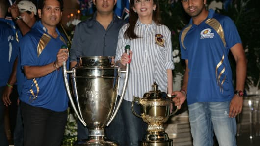 Sachin Tendulkar and Nita Ambani pose with the trophy during the party hosted for Mumbai Indians team for their victory in Champions League T20, October 7, 2013